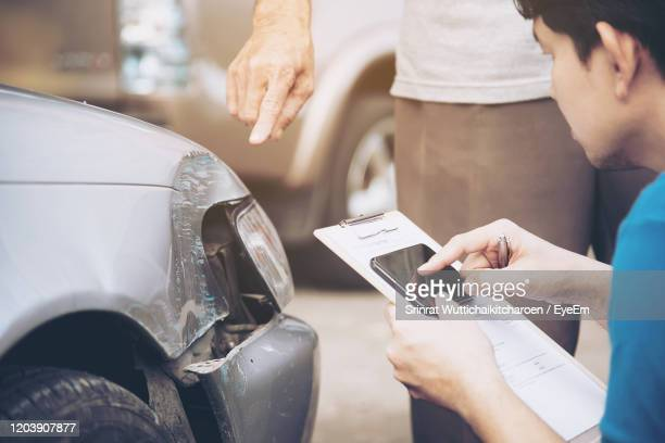 man holding mobile phone and paper by customer showing damaged car - car insurance stock pictures, royalty-free photos & images