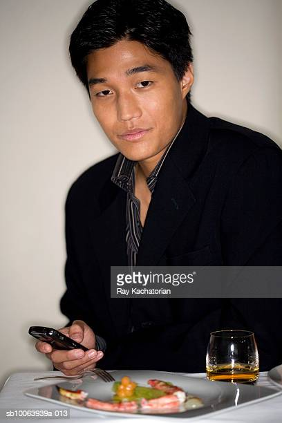 Man holding mobile phone in restaurant, portrait