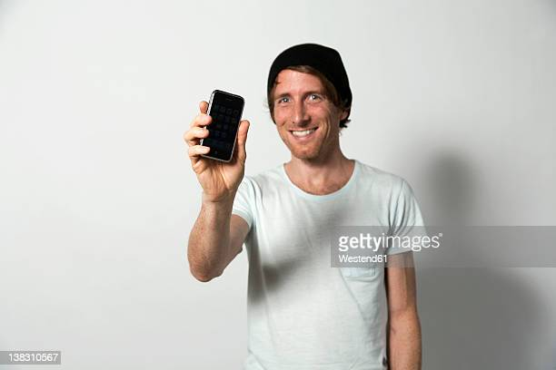 man holding mobile phone, smiling - tonen stockfoto's en -beelden