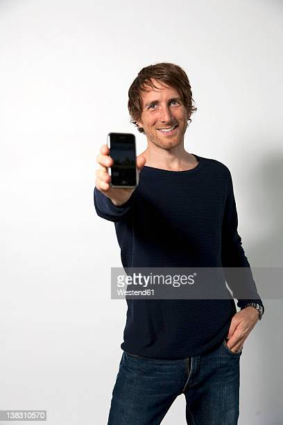Man holding mobile phone, smiling