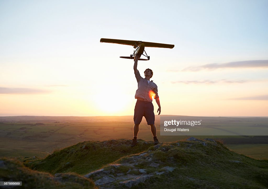 Man holding model air plane over head at sunset. : Stock Photo