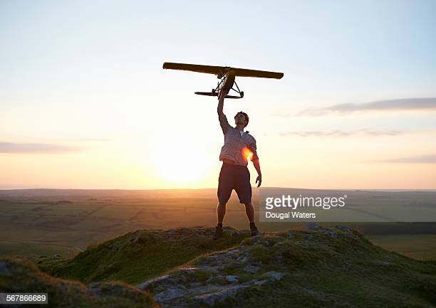 Man holding model air plane over head at sunset.