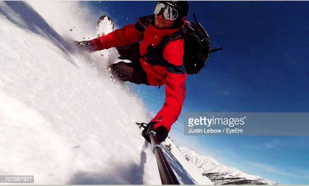 Man Holding Monopod While Skiing At Snow Covered Mountain Against Blue Sky During Winter