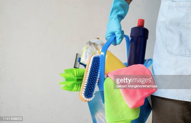 man holding mop and plastic bucket with brushes, gloves and detergents in the kitchen - きれいにする ストックフォトと画像