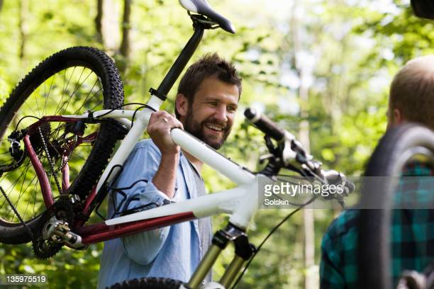 man holding mountainbike over shoulder