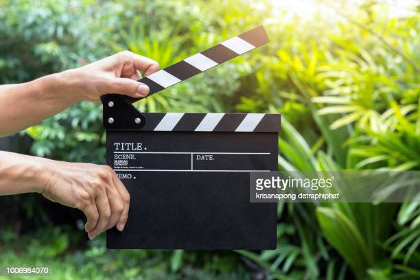 a man holding movie clapper. - clapboard stock pictures, royalty-free photos & images