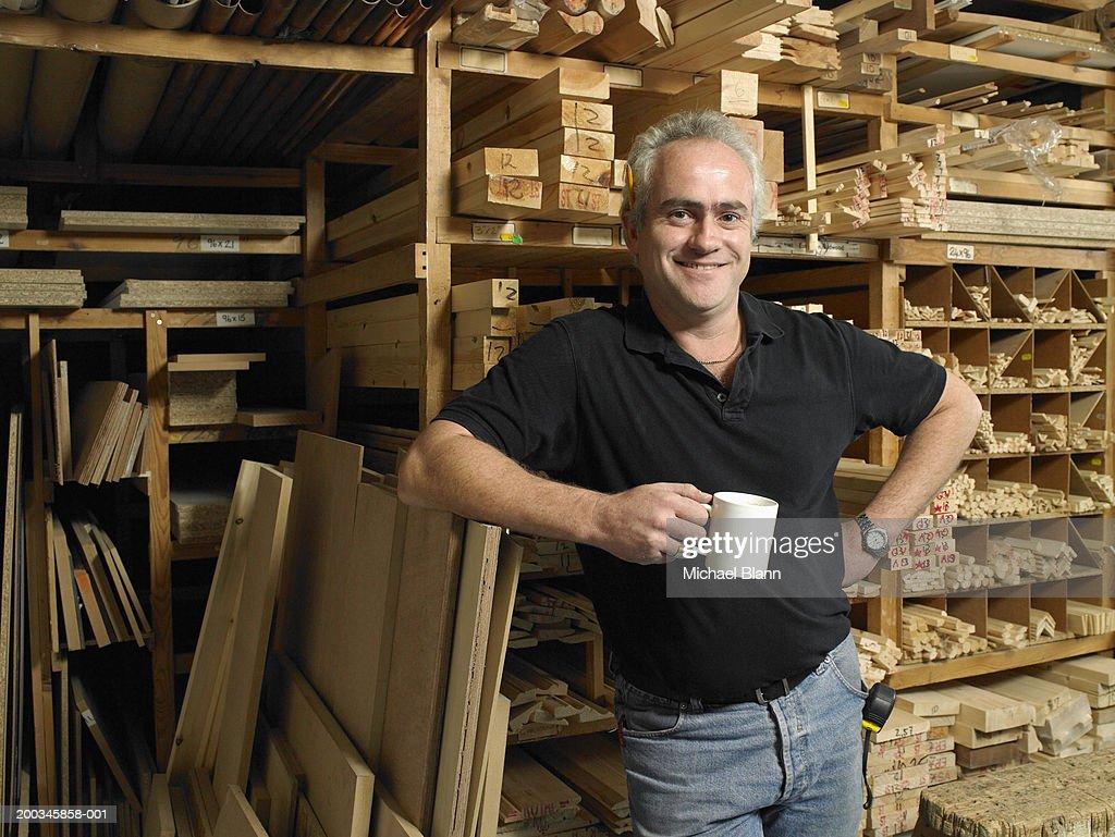 Man holding mug by planks of wood on shelves, smiling, portrait : Stock Photo