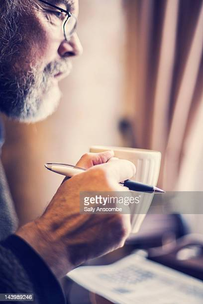 Man holding mug of tea and pen