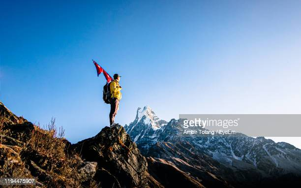 man holding nepali flag while standing on mountain against clear blue sky - pokhara stock pictures, royalty-free photos & images