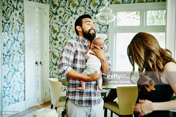 Man holding newborn baby for friend in kitchen