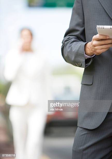man holding notebook, partial view, silhouette of woman in suit in background - out of frame stock pictures, royalty-free photos & images