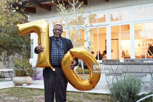 man holding number 70 helium balloons in backyard - 70 79 jaar stockfoto's en -beelden