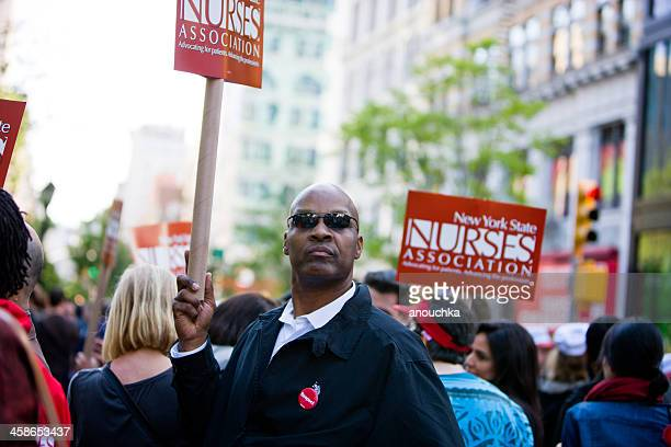 man holding ny nurses association banner on union square - may day international workers day stock photos and pictures