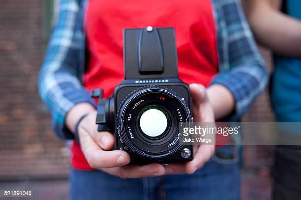 man holding old camera, toronto, canada - jake warga stock pictures, royalty-free photos & images