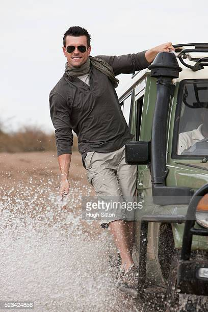 man holding on to car driving though water - hugh sitton stock pictures, royalty-free photos & images
