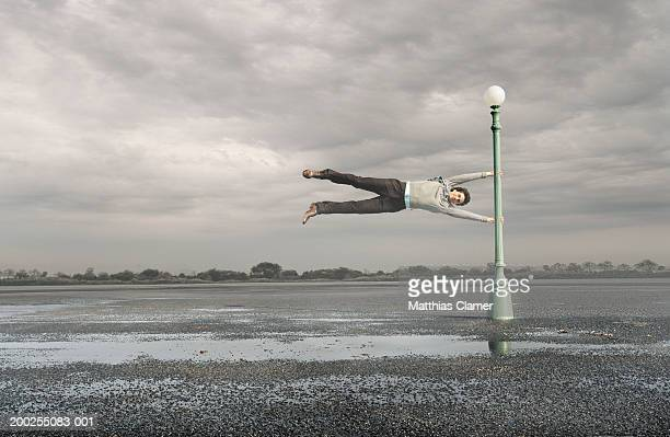 Man holding on to lamp post in mid air, portrait