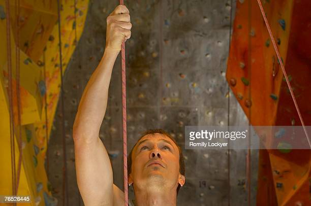 Man holding onto rope at indoor climbing centre, close-up
