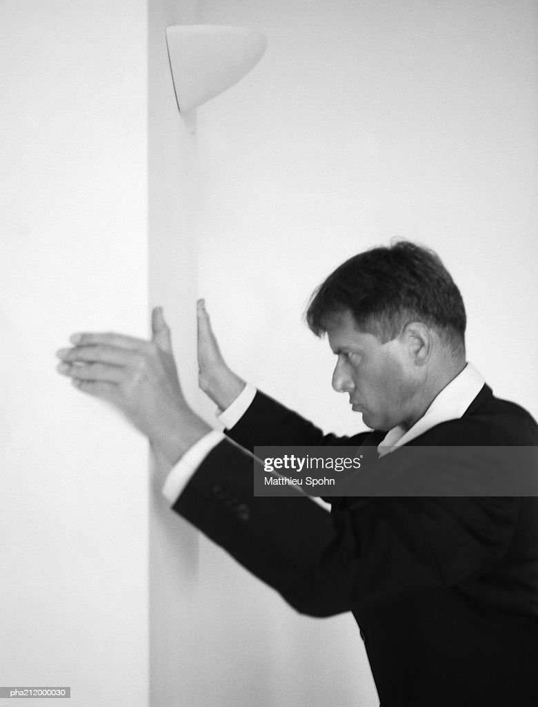 Man holding onto the wall, side view, b&w. : Stockfoto