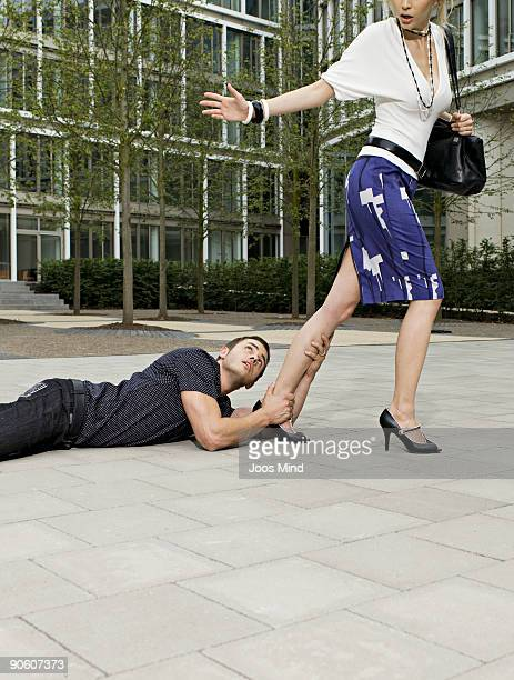 man holding onto womans leg, as she walks away - suplicar imagens e fotografias de stock