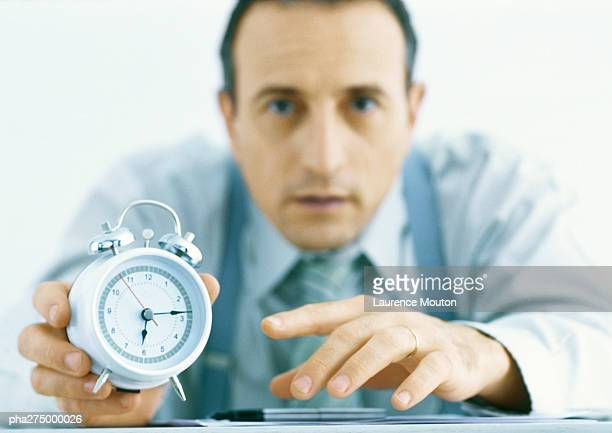 Man holding out alarm clock, focus on hands and clock in foreground