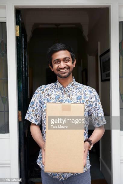 man holding package in doorway - door stock pictures, royalty-free photos & images