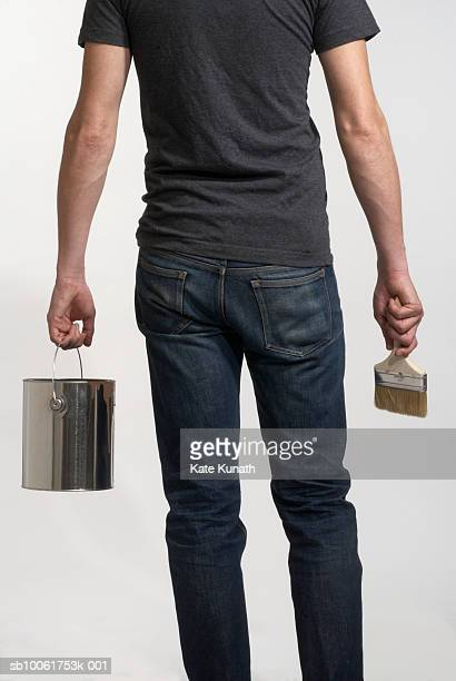 Man holding paint can in one hand and a brush in the other, rear view
