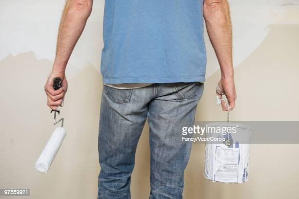 Man holding paint roller and can of paint
