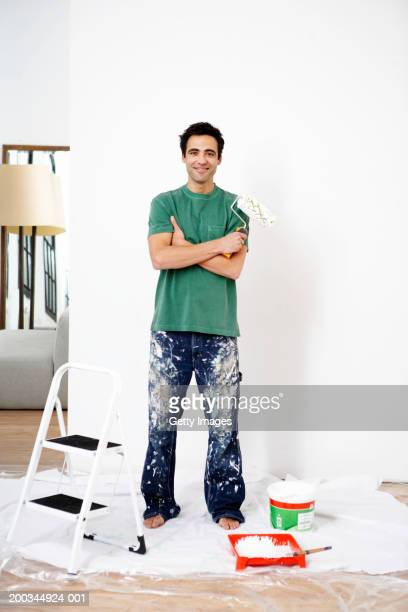 Man holding paint roller by step ladder indoors, smiling, portrait
