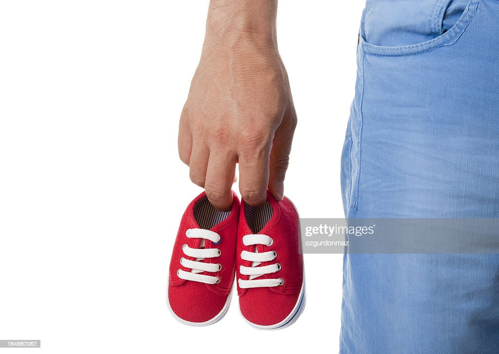 Man holding pair of baby shoes : Stock Photo