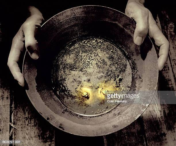 man holding pan containing nuggets of gold, close-up (tinted b&w) - gold rush stock photos and pictures