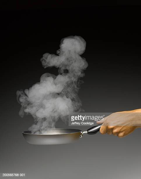 Man holding pan in hand, close-up