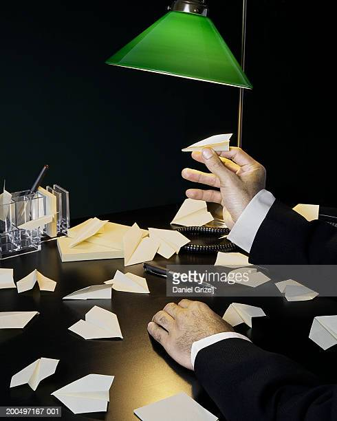 Man holding paper airplanes on desk