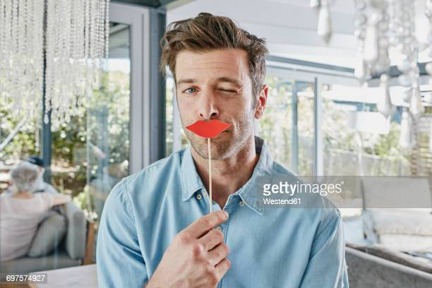 man holding paper lips in front of his mouth - flirtare foto e immagini stock