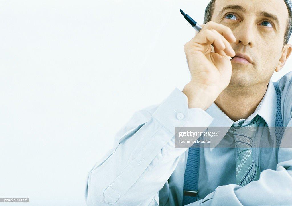Man holding pen near face, looking up : Stockfoto