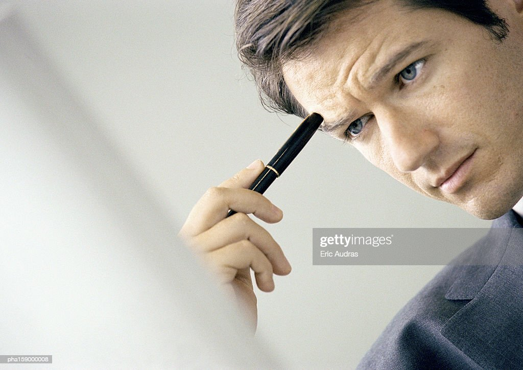 Man holding pen to head, partial view, blurred rear view of computer screen in foreground. : Stockfoto