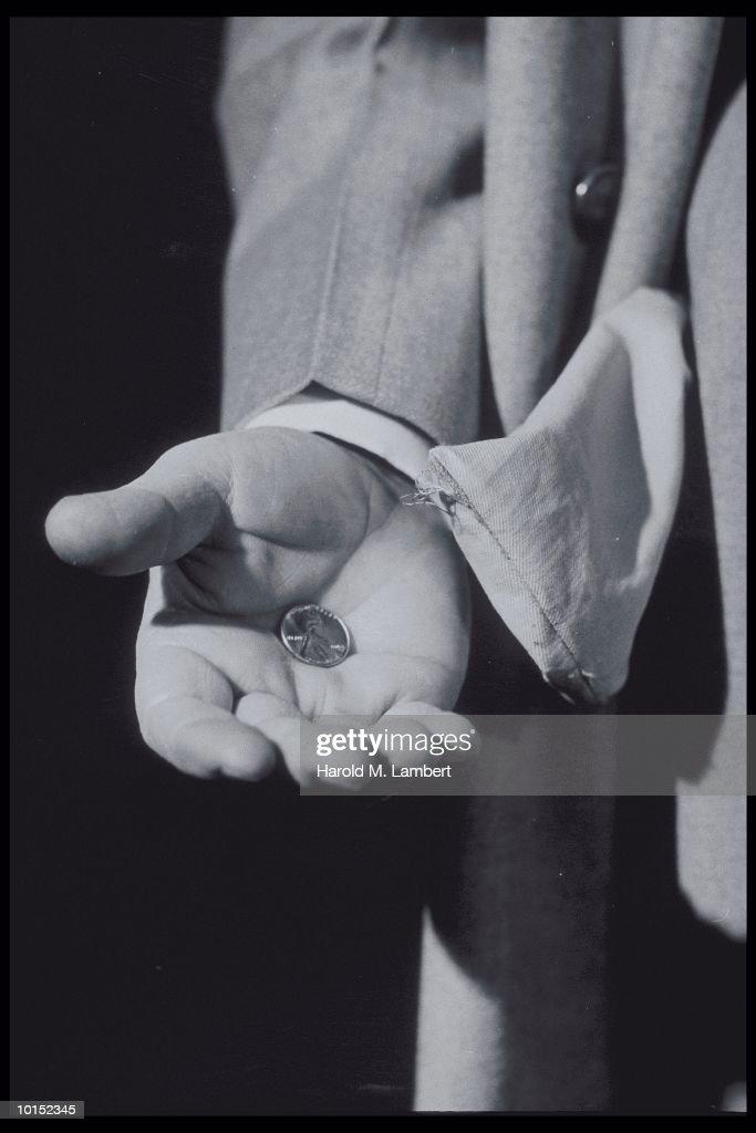 Man holding penny by empty pocket close-up (B&W) : Stockfoto