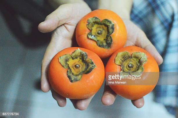 Man Holding Persimmon Fruit