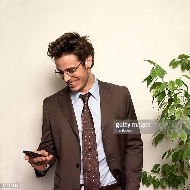 Man holding phone in office, smiling