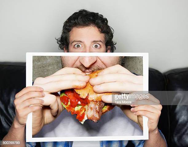 man holding picture of junk food