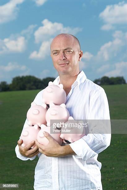 man holding piggy banks - só um homem maduro imagens e fotografias de stock