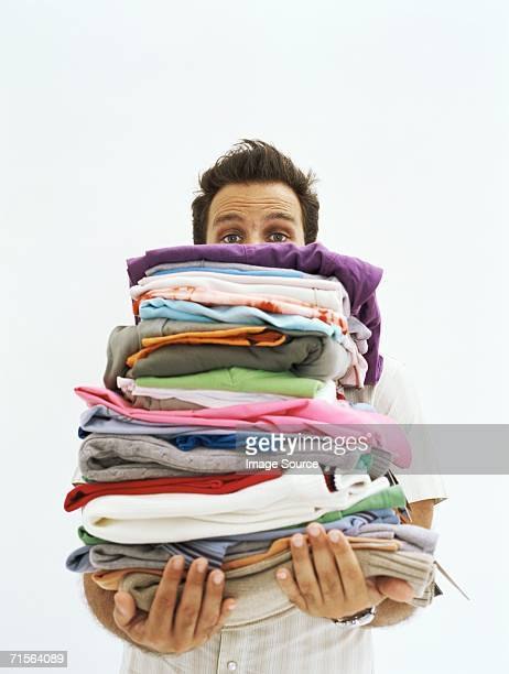 man holding piles of clothes - commercial activity stock pictures, royalty-free photos & images