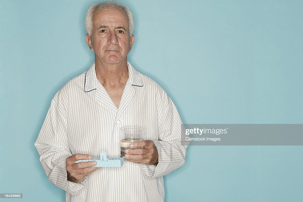 Man holding pill case and glass of water : Foto de stock