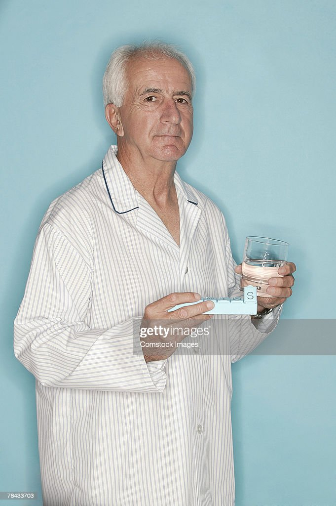Man holding pill case and glass of water : Stockfoto