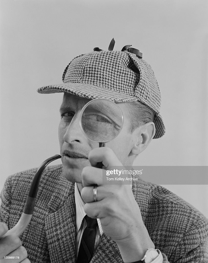 Man holding pipe and looking through magnifying glass : Stock Photo