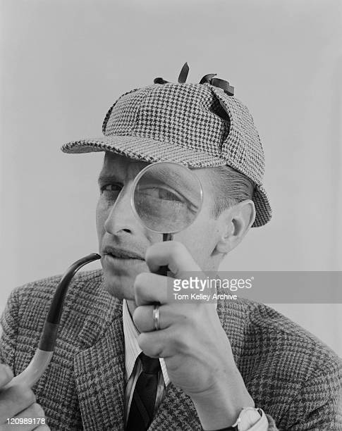man holding pipe and looking through magnifying glass - archival stock pictures, royalty-free photos & images
