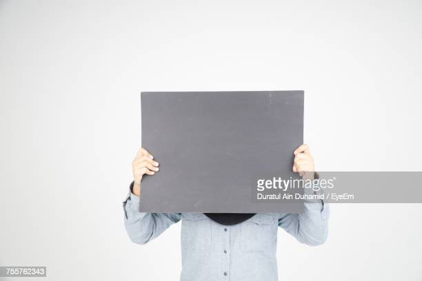 Man Holding Placard In Front Of Face While Standing Against White Background
