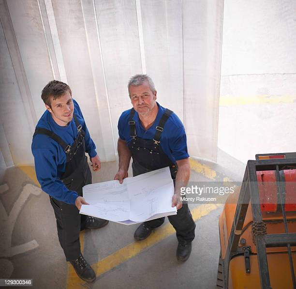 man holding plans next to fork lift in joinery - カバーオール ストックフォトと画像
