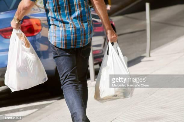 ビニール袋を持ち、通りを歩いている男。 - ビニール袋 ストックフォトと画像