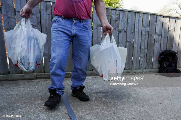 man holding plastic shopping bags - carrying stock pictures, royalty-free photos & images