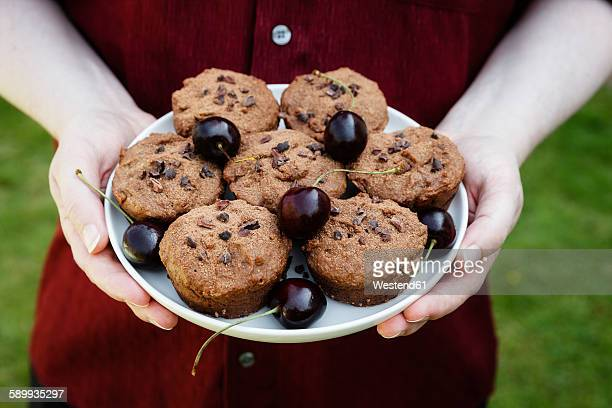 Man holding plate with vegan chocolate muffins with cherries